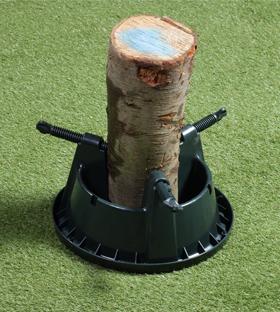 Uz grīdas nolikts mini plastmasas statīvs, kurā iestiprināts koka stumbra fragments