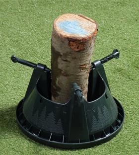 Uz grīdas nolikts mazais plastmasas statīvs, kurā iestiprināts koka stumbra fragments