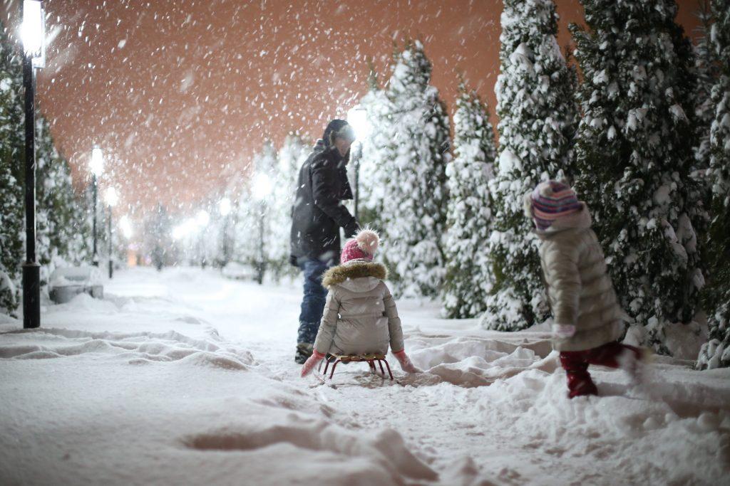 Tēvs un 2 bērni bauda ziemas priekus, braucot ar ragaviņām