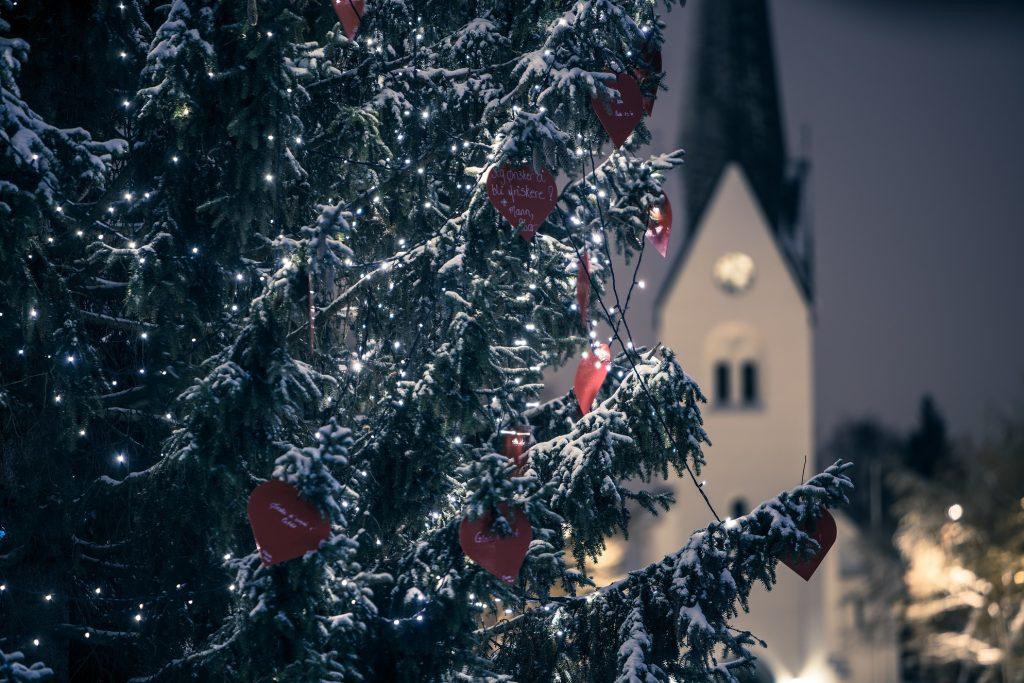 Tuvplānā liela, dekorēta, apsnigusi Ziemassvētku egle, fonā baznīca