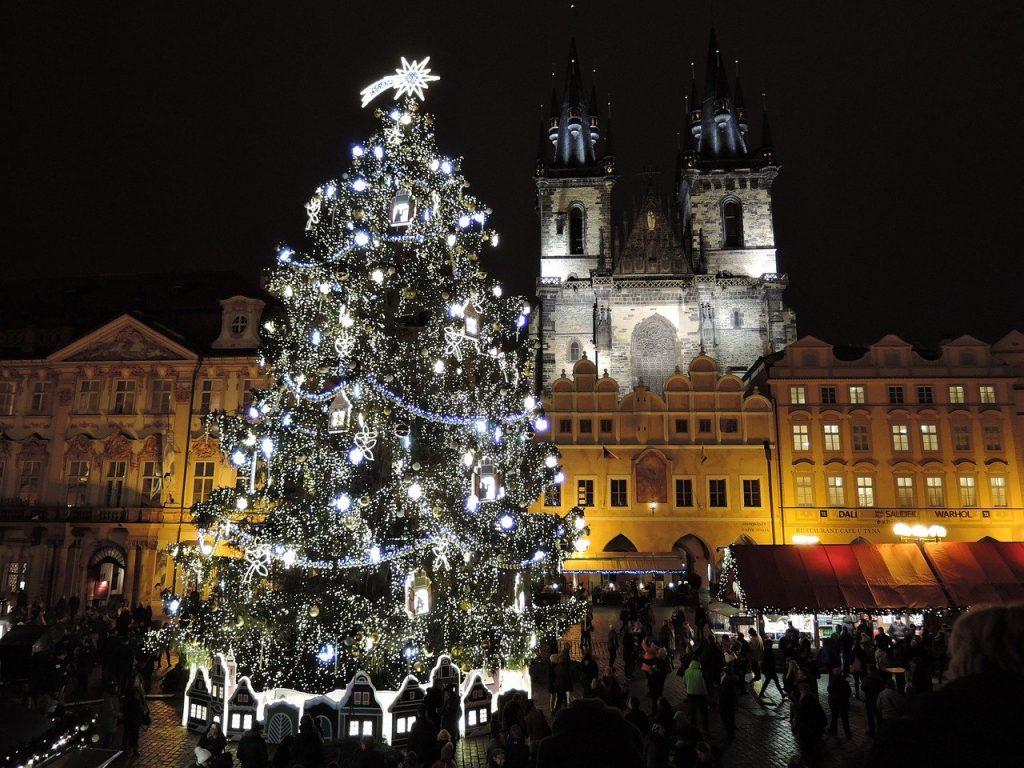 Ar lampiņām dekorēta svētku egle Prāgā vakarā