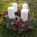 Adventes vainags no Nobilis egļu zariem ar sarkanām dekorācijām un baltām svecēm