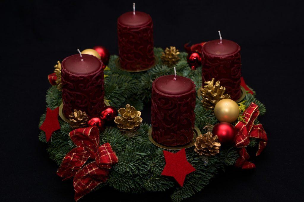 Adventes vainags ar 4 tumši sarkanām svecēm, kas iestiprinātas vainagā ar speciāliem svečturiem, un sarkanām dekorācijām