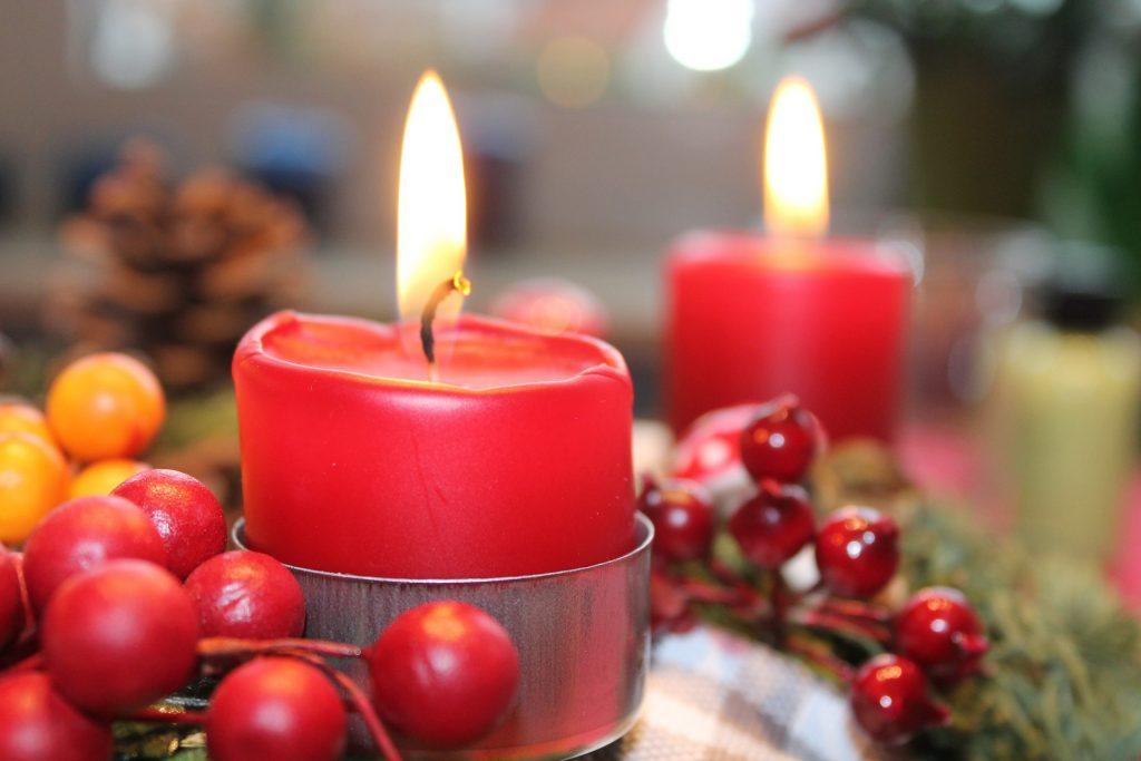 Bildē redzamas divas sarkanas Adventes vainaga sveces
