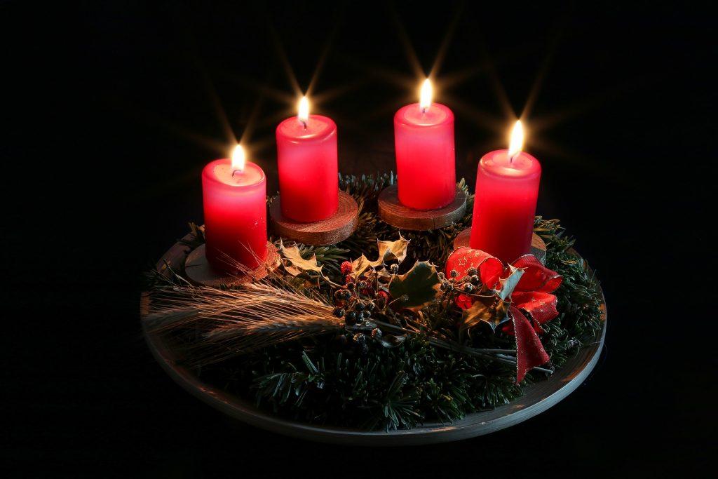 Adventes vainags ar sarkanām svecēm, kas iestiprinātas koka svečturos.