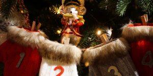 Adventes kalendārs, kur katrai dienai ir sava vilnas zeķe ar datumu un dāvaniņu, fonā ir egle un dekoratīva peles figūriņa