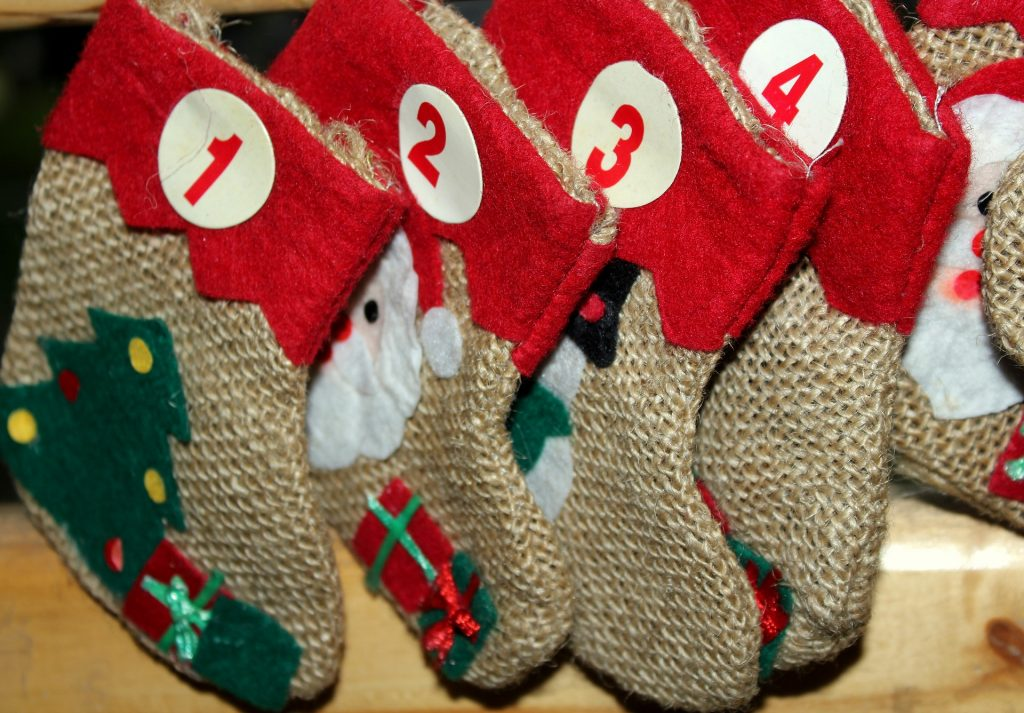 Virtenē sastiprinātas Ziemassvētku zeķes ar datumiem, kas izmantotas kā Adventes kalendārs