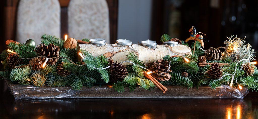 Adventes kompozīcija, kurā kā svečturis izmantota bērza koka pagale, kurā iestrādātas sveces