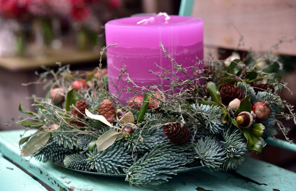 Atventes vainags ar lielu, lillā sveci un citu augu dekorācijām - zariņiem u.tml.