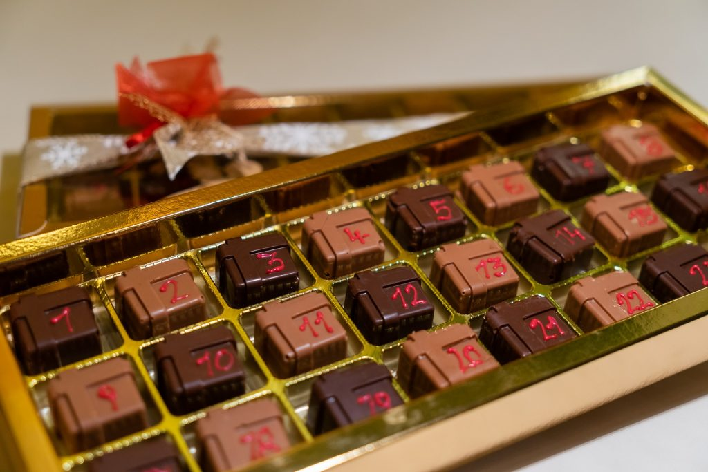 Šokolādes konfektes kartona kastē, katrai konfektei virsū ir datums no 1. līdz 24.