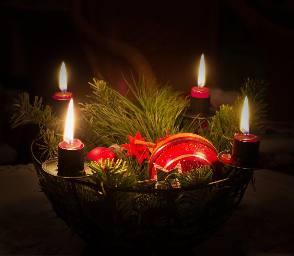Metāla svečturis, kurā iestiprinātas 4 sveces un egļu zari