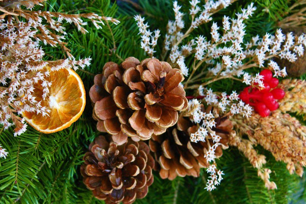 Adventes vainaga dekorācijas tuvplānā - čiekuri, sausie ziedi, citrusaugļu šķēlītes, ogas