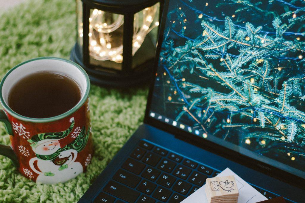 dators ar Ziemassvētku egles zariem, Ziemassvētku krūze ar tēju un lukturis ar lampiņām